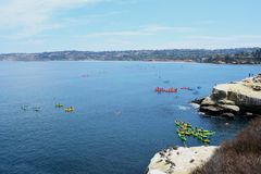 La Jolla Cove kayak tours. Distant view of kayak tours being conducted in La Jolla Cove and a view of the surrounding landscape, located in La Jolla, San Diego stock photography