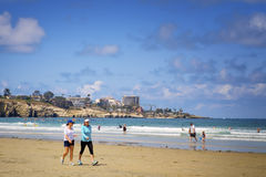 La Jolla Shores Beach, California. Women walk and people play in the water of the La Jolla Shores beach, on the Pacific Ocean, a popular tourist and vacation stock image