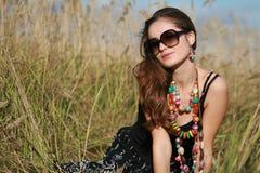 La joyería y las gafas de sol que desgastan de la muchacha se sienta en campo Imágenes de archivo libres de regalías