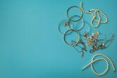 La joyería y la otra materia de las mujeres en un fondo azul fotografía de archivo libre de regalías