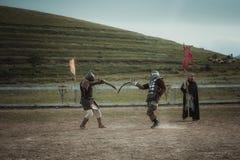 La justa medieval knights en cascos y batalla del correo en cadena en la espada Imágenes de archivo libres de regalías