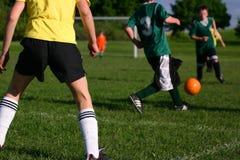 La juventud embroma el juego de fútbol en día asoleado caliente Fotografía de archivo libre de regalías