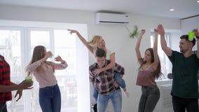 La juventud está engañando alrededor en un partido casero, los muchachos y las muchachas están bailando y se están divirtiend metrajes