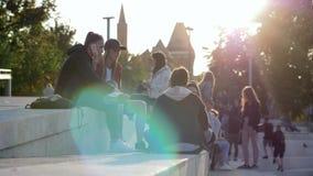 La juventud urbana habla en el teléfono durante el tiempo libre en la plaza en luz del sol el fin de semana metrajes