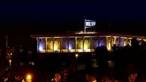 La Knesset avec le drapeau de ondulation de vol de l'Israël la nuit clips vidéos