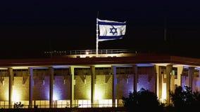 La Knesset avec le drapeau de ondulation de vol de l'Israël la nuit banque de vidéos