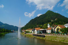 Laško, Slovenija. Medieval city of Laško on the banks of Savinja river on sunny summer day with large fountain in the middle of the river Royalty Free Stock Photography