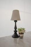 La lámpara blanca y la flor adornan en la tabla Fotografía de archivo
