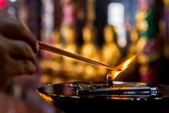 La lámpara de aceite grande con la mano toma un backgr encendido del palillo y de Buda de ídolo chino Fotografía de archivo