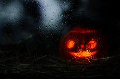 La lámpara de Jack es visible a través del vidrio mojado imagen de archivo libre de regalías