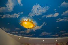 La lámpara en el techo en el cuarto de niños bajo la forma de sol Fotos de archivo libres de regalías