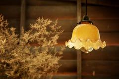 La lámpara retra de la ejecución en estilo del vintage con la pared de madera áspera adorna por la loza de barro de la hierba sec Fotografía de archivo libre de regalías