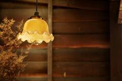La lámpara retra de la ejecución en estilo del vintage con la pared de madera áspera adorna por la loza de barro de la hierba sec Imágenes de archivo libres de regalías