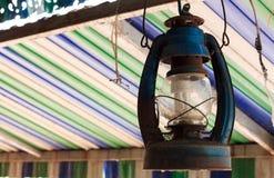La lámpara vieja cuelga en fondo colorido del haz Imagen de archivo libre de regalías
