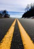 La línea amarilla abajo de una carretera Foto de archivo