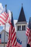 La línea de banderas americanas coloca la iglesia blanca exterior en Memorial Day Fotos de archivo libres de regalías
