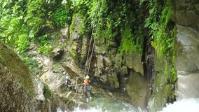 La línea de la cremallera sobre la cascada envía la chica joven mientras que descenso de cañones almacen de metraje de vídeo