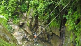La línea de la cremallera sobre la cascada envía el muchacho joven mientras que descenso de cañones almacen de metraje de vídeo