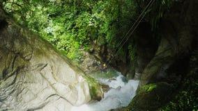 La línea de la cremallera sobre la cascada envían las mujeres turísticas mientras que descenso de cañones almacen de metraje de vídeo