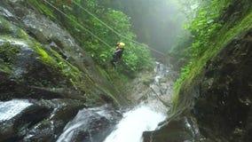 La línea de la cremallera sobre la cascada envían las mujeres turísticas mientras que descenso de cañones almacen de video