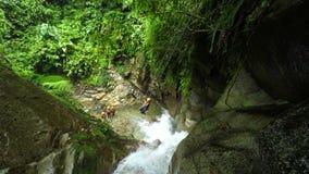 La línea de la cremallera sobre la cascada envían las mujeres turísticas mientras que descenso de cañones metrajes