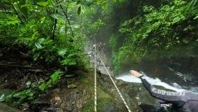 La línea de la cremallera sobre la cascada envían los hombres jovenes asiáticos turísticos mientras que descenso de cañones almacen de video