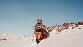 La línea delgada de escaladores pasa a través de la trayectoria profunda hacia la montaña que tienen que conquistar metrajes