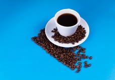 La línea diagonal se hace de los granos de café; una taza con un platillo se llena de café sobre la línea fotos de archivo libres de regalías