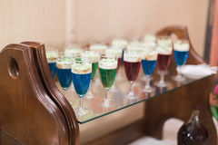 La línea hermosa de diversos cócteles coloreados en la tabla del ramo del abastecimiento sirvió para el partido Fotografía de archivo