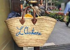 La L ` Occitane ha marcato a caldo la borsa della paglia che appende sulla porta del deposito Fotografia Stock