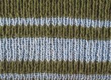 La laine de vert olive a tricoté à la main la texture avec les rayures bleu-clair ab Photographie stock libre de droits