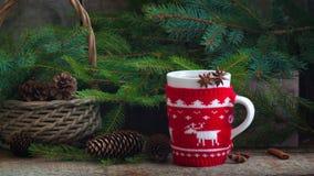 La laine faite main de Noël tricotée a enveloppé la tasse avec le fond rustique de cannelle de pins de cônes de thé Images stock