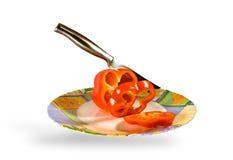 La lama taglia il pepe su un piatto Fotografie Stock