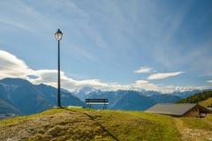 La lampada, bench una piccola capanna in alpi svizzere Posto ideale da sedersi ed en Fotografia Stock Libera da Diritti