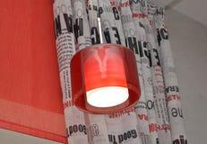 La lampada con un plafond rosso contro un portiere e un rolshtor immagine stock libera da diritti