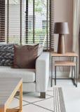 La lampada da tavolo di legno sulla tavola di legno accanto al sofà ha messo in salone Fotografie Stock
