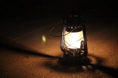 La lampada di cherosene si accende in uno scuro vicino ad una parete di pietra Fotografie Stock Libere da Diritti
