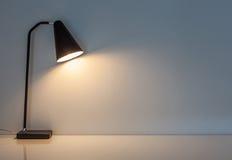 La lampada di scrittorio moderna si illumina sui precedenti della parete Fotografia Stock Libera da Diritti
