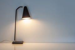 La lampada di scrittorio moderna si illumina sui precedenti della parete Immagine Stock Libera da Diritti