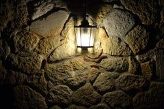 La lampada di via illumina la parete di pietra alla notte Fotografia Stock