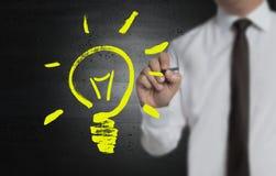 La lampadina è dipinta dall'uomo d'affari sullo schermo immagine stock libera da diritti