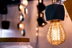La lampadina bruciante splende debolmente sulle luci romantiche gialle vaghe fondo fotografie stock libere da diritti
