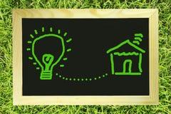 La lampadina connette con la casa sulla lavagna Fotografie Stock Libere da Diritti