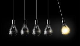 La lampadina d'ardore è fra molte lampadine spente su fondo blu scuro, l'idea di concetto, il concetto di moto perpetuo, una a Fotografie Stock