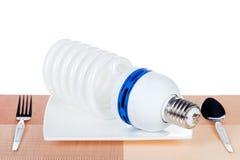 La lampadina sul piatto ha isolato Immagini Stock
