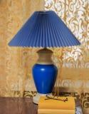 La lampe avec l'ombre, un livre et une fenêtre avec un rideau Photographie stock libre de droits
