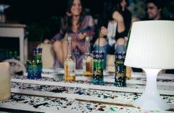 La lampe blanche au-dessus de la table de palettes avec des confettis dans l'extérieur font la fête Photographie stock