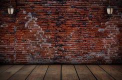 La lampe sur les murs de briques rouges et les vieux planchers en bois Images libres de droits