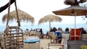 La lampe vide dans une barre ou un café de plage balance sur une brise marine sur un bord de la mer de la Mer Noire Mer brouillée banque de vidéos