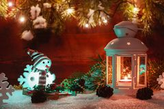 La lanterna bianca con una candela bruciante sta nella neve circondata dalle decorazioni di Natale sui precedenti di un di legno fotografia stock libera da diritti